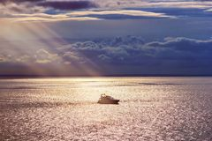 Lonely ship at sunset lit by the rays of the sun royalty free stock photography