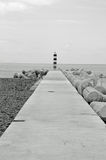A lonely shore beacon black and white. A shore beacon at the end of pavement somewhere in Funchal Stock Photo