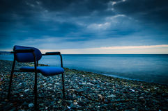 Lonely Shoreline. Concept of loneliness with muted colors on a cold empty shoreline with an empty chair and storm clouds in the sky Royalty Free Stock Images