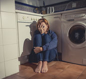 Lonely and sick woman sitting on kitchen floor in stress depression and sadness Royalty Free Stock Photo