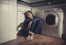 Lonely and sick woman sitting on kitchen floor in stress depression and sadness Stock Photos