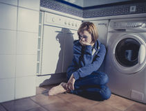 Lonely and sick woman sitting on kitchen floor in stress depression and sadness Royalty Free Stock Photos
