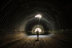 Lonely silhouette in dark tunnel goes to the light . Man walking to the light . royalty free stock photography