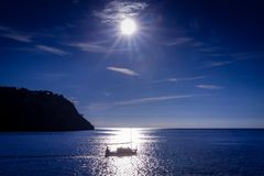 A lonely silhouette of a fishing boat. A beautiful relaxing tranquil scene of a lonely fishing boat Stock Photography