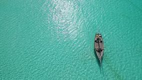 Lonely sitting near shore at noon, aerial. Lonely rustic wooden boat sitting near the shore at sunny noon, aerial stock video footage