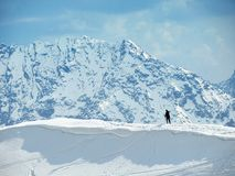 Lonely skier. Climbing mountain summit in winter royalty free stock photo