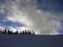 Lonely skier on a ridge of a ski slope. With blue sky and clouds Stock Photo