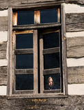 Lonely small baby girl behind window stock images