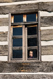 Lonely small baby girl behind window royalty free stock image
