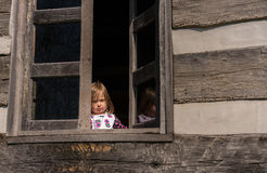 Lonely small baby girl behind window stock photo