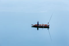 A lonely small boat with two young fishermen Stock Photos