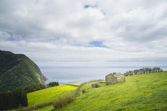 Lonely small cabin on the edge of the azores island in portugal with a great view to the atlantic ocean and cloudy sky stock photography