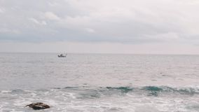 Lonely small fishing boat in sea. Old fisherman sailing in open sea. Man is fishing at storm. Fishing ship swaying on big waves. S. Mall boat swaying in open sea stock video footage