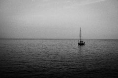 Lonely small sail boats at dusk of the coast of Italy. Lonely small sail boats at dusk of the coast of Moneglia, Cinque Terre,  Italy - grainy film image Stock Photography