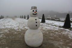 Lonely smiling snowman with a pot on his head and with a carrot on his nose in a fog Stock Photography