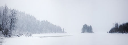 Lonely snow-covered island on a frozen lake Royalty Free Stock Photo