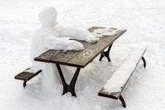 Lonely snow man sitting at picnic table Stock Photo