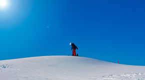 A Lonely Snowboarder on a Hill. A Snowboarder climbing up a small snowy hill Stock Images