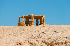 A lonely standing yellow stone arbor, standing alone in the desert on a hill. Against the background of a cloudless blue sky Stock Photos