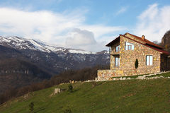 Lonely stone house on the hill on the background of snowy mountains, horizontal Royalty Free Stock Photography