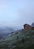 Lonely stone house on the hill on the background of snowy mountains, overcast, dark Stock Image