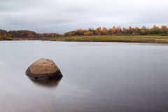 Lonely stone in water in Autumn in Russia. Amazing landscape of far North of Russia Royalty Free Stock Image