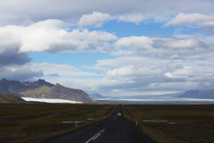 Lonely straight road. With car and unreal background nature with Iceland glacial Royalty Free Stock Photography