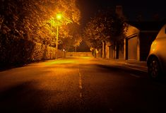 A Lonely Street. A warm but melancholy atmosphere descends on this quiet street, lit only by a single streetlight, scattering it's rays across the tarmac Stock Images