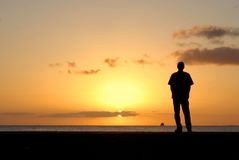 Lonely Sunset. A man stands alone, watching the sunset at the beach Royalty Free Stock Image
