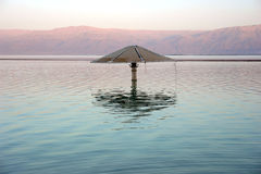 Lonely sunshade  in the middle of the Dead Sea Stock Photos