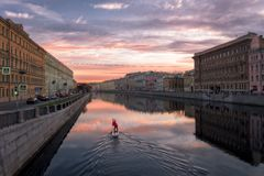 Lonely sup surfer moves along the Fontanka river at dawn stock photos