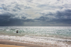 Lonely surfboarder heading out to the waves Royalty Free Stock Photography