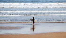 A lonely surfer enjoying her time at San Lorenzo beach during a sunny Easter morning, Gijon, Asturias, Spain royalty free stock photos