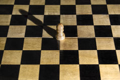 Isolation concept. Lonely isolated survivor pawn on empty chess board Royalty Free Stock Photos