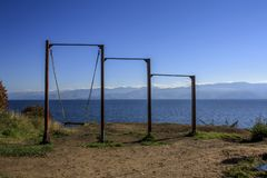 Lonely swing on the background of Lake Baikal and the mountains royalty free stock photo