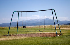 Lonely Swing Set. A lonely swing set facing a beautiful mountain range Royalty Free Stock Photography