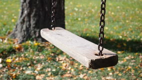 Lonely swing sways in the wind, surrounded by trees in autumn park. Golden foliage around. Swing is made of wooden. Planks and hanging on the iron chains stock footage