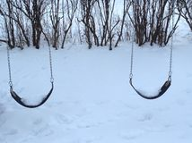 Lonely swings. Swings in the snow Royalty Free Stock Photo