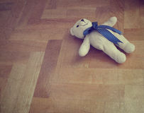 Lonely teddy bear on the floor - retro styled Stock Photo