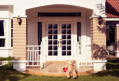 Lonely teddy bear. Sitting on house porch Royalty Free Stock Image