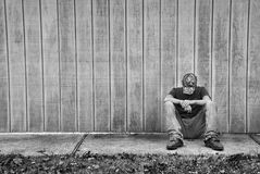 Lonely Teen. A sad/thinking teen boy sitting against a wall Stock Images