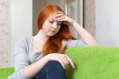 Lonely teen girl sits on sofa Royalty Free Stock Images