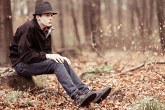 Lonely teen in hat staring ahead in woods. Lonely single male teenager wearing hat and jacket while sitting on tree stump in forest staring ahead Stock Photos