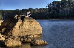 Lonely teen in hoodie texting on cell phone, Lake Allatoona, Red Top Mountain State Park, Georgia, USA royalty free stock photo