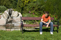 Lonely teenage boy. A teenage boy sitting alone on a park bench, thoughtful Royalty Free Stock Photography
