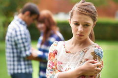 Lonely Teenage Girl Jealous Of Couple In Background Royalty Free Stock Image