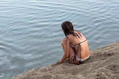 Lonely teenage girl sitting on the beach Royalty Free Stock Photo