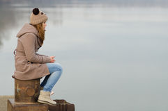 Lonely teenage girl sitting on the dock stock photo