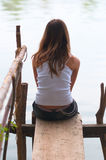 Lonely teenage girl sitting on the small dock. Beside the river stock photography