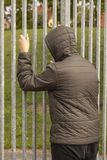 Lonely teenager standing outside a metal fence with iron bars and looking inside. Loneliness and bullying concept. Stock image stock photo